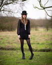 Beautiful young woman dressed in black wearing bowler hat portrait of a a dress nylons boots and a standing a country farm field Stock Photos