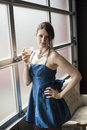 Beautiful young woman drinking a pink martini with brown hair and eyes in blue satin cocktail dress she is Royalty Free Stock Image