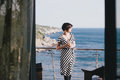 Beautiful young woman drinking wine on a balcony with beautiful ocean view wearing black and white dress and standing Stock Images