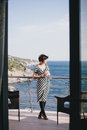 Beautiful young woman drinking wine and standing on a balcony with beautiful ocean view wearing black white dress Stock Photos