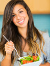 Beautiful young woman eating a bowl of healthy organic salad portrait and smiling Royalty Free Stock Photos