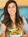 Beautiful young woman eating a bowl of healthy organic salad portrait and smiling Stock Photography