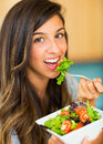 Beautiful young woman eating a bowl of healthy organic salad Royalty Free Stock Photo