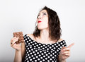 Beautiful young woman eating a chocolate bar, wears a dress with polka dots. expresses different emotions Royalty Free Stock Photo