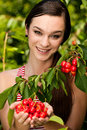 Beautiful young woman eats cherry on plantation Royalty Free Stock Photo
