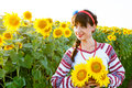 Beautiful young woman in  embrodery holding three sunflowers Royalty Free Stock Photo