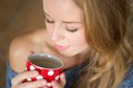 Beautiful young woman enjoying cup of tea at home close up portrait a Stock Photography