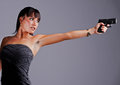 A beautiful young woman in a fashionable evening dress holds her firearm as she prepares to shoot and defend herself Stock Image