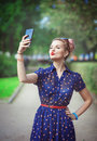 Beautiful young woman in fifties style taking picture of herself outdoor Royalty Free Stock Images