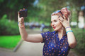 Beautiful young woman in fifties style taking picture of herself outdoor Stock Image