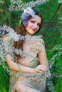 Beautiful young woman with a flower in hairs in spring forest Royalty Free Stock Photography
