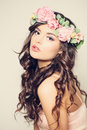 Beautiful Young Woman with Flowers. Long Curly Hair Royalty Free Stock Photo
