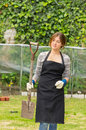Beautiful young woman gardening holding a spade outdoors Royalty Free Stock Photography
