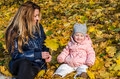 Beautiful young woman girl happy mother playing with her daughter smiling and holding a yellow maple leaves walking in autumn park Royalty Free Stock Photo