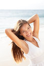 Beautiful young woman girl relaxing on beach smiling happy and joyful during summer holidays travel vacation smiling mixed race Royalty Free Stock Photography