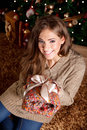 Beautiful young woman giving a christmas gift in front of tree Stock Photo