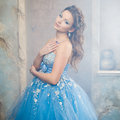 Beautiful young woman in gorgeous blue long dress like Cinderella with perfect make-up and hair style Royalty Free Stock Photo