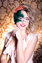 Beautiful young woman in a green mysterious venetian mask a new year carnival christmas masquerade a dance club secret nigh the Stock Photo