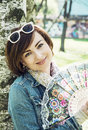 Beautiful young woman with hand fan is leaning on the birch tree in park beauty fashion and nature Royalty Free Stock Photo
