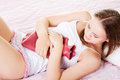 Beautiful young woman have stomach ache is lying on the bed with hot water bottle Royalty Free Stock Images