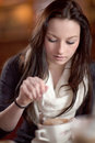 Beautiful young woman having delicious dinner cup frothy cappuccino coffee restaurant Royalty Free Stock Image