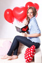 Beautiful young woman with heart shaped balloons writing a love card Royalty Free Stock Photo