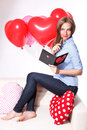 Beautiful young woman with heart shaped balloons writing a love card Royalty Free Stock Images