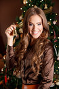 Beautiful young woman holding a bell at christmas eve int front of the tree Royalty Free Stock Photo