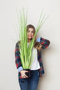 Beautiful young woman holding big green plant Royalty Free Stock Photo