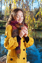 Beautiful young woman holding a coffee cup portrait of with closed eyes walking in autumn park near lake Stock Images
