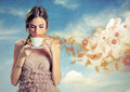 Beautiful young woman holding a cup of tea over a sky background Royalty Free Stock Photo