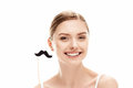 Beautiful young woman holding fake moustache on stick, skin care concept