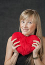 Beautiful young woman holding a heart shaped red vertical shot of the pillow and smiling Royalty Free Stock Photography