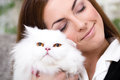 Beautiful young woman holding a Persian cat Royalty Free Stock Photo
