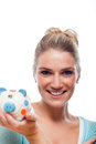 Beautiful young woman holding a piggy bank blond colourful polka dot in her hand smiling in anticipation of realising her goals Stock Photography