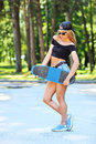 Beautiful young woman holding a skateboard outdoors Stock Photos
