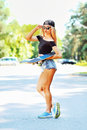 Beautiful young woman holding a skateboard outdoors Royalty Free Stock Photography
