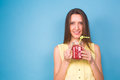 Beautiful young woman holding strawberry smoothie on blue background. Healthy organic drinks concept. People on a diet. Royalty Free Stock Photo