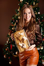 Beautiful young woman holding a wrapped gift in front of the christmas tree Royalty Free Stock Photography