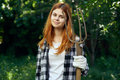 Beautiful young woman holds a fork for working in the garden, summer, gardener