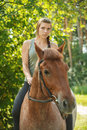 Beautiful young woman on horseback portrait of against green of summer park Royalty Free Stock Photos