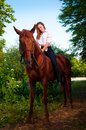 Beautiful young woman on horseback riding chestnut horse Stock Photo