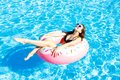 Beautiful young woman on inflatable donut in swimming pool Royalty Free Stock Photo