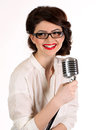 Beautiful young woman isolated on white in studio in old fashion clothes representing pinup and retro style with microphone Royalty Free Stock Photo