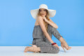 Beautiful Young Woman In Jumpsuit And White Sun Hat Is Sitting And Looking Away Over Shoulder Royalty Free Stock Photo