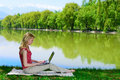 Beautiful young woman with laptop near the lake Stock Photography
