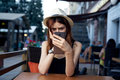 Beautiful young woman in a light hat at a table in the summer in a cafe on the terrace holding a phone Royalty Free Stock Photo