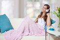 Beautiful young woman listening to music on the sofa Royalty Free Stock Photo