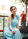 Beautiful young woman in a long blue dress in anticipation thoughtfully looking up Stock Image