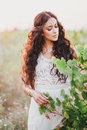 Beautiful young woman with long curly hair dressed in boho style dress posing in a field with dandelions Royalty Free Stock Photo